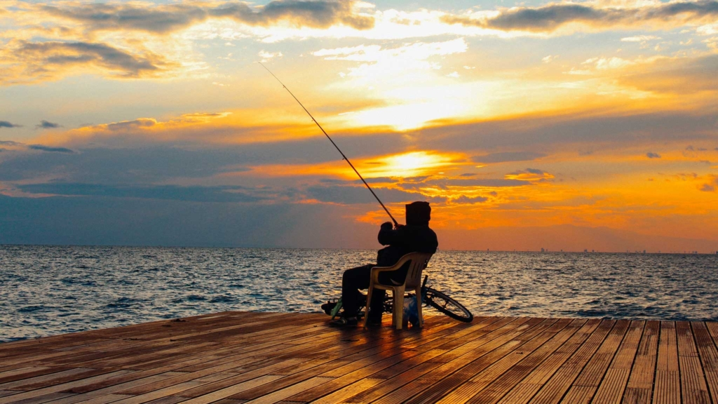 рыбак ловит рыбу на закате