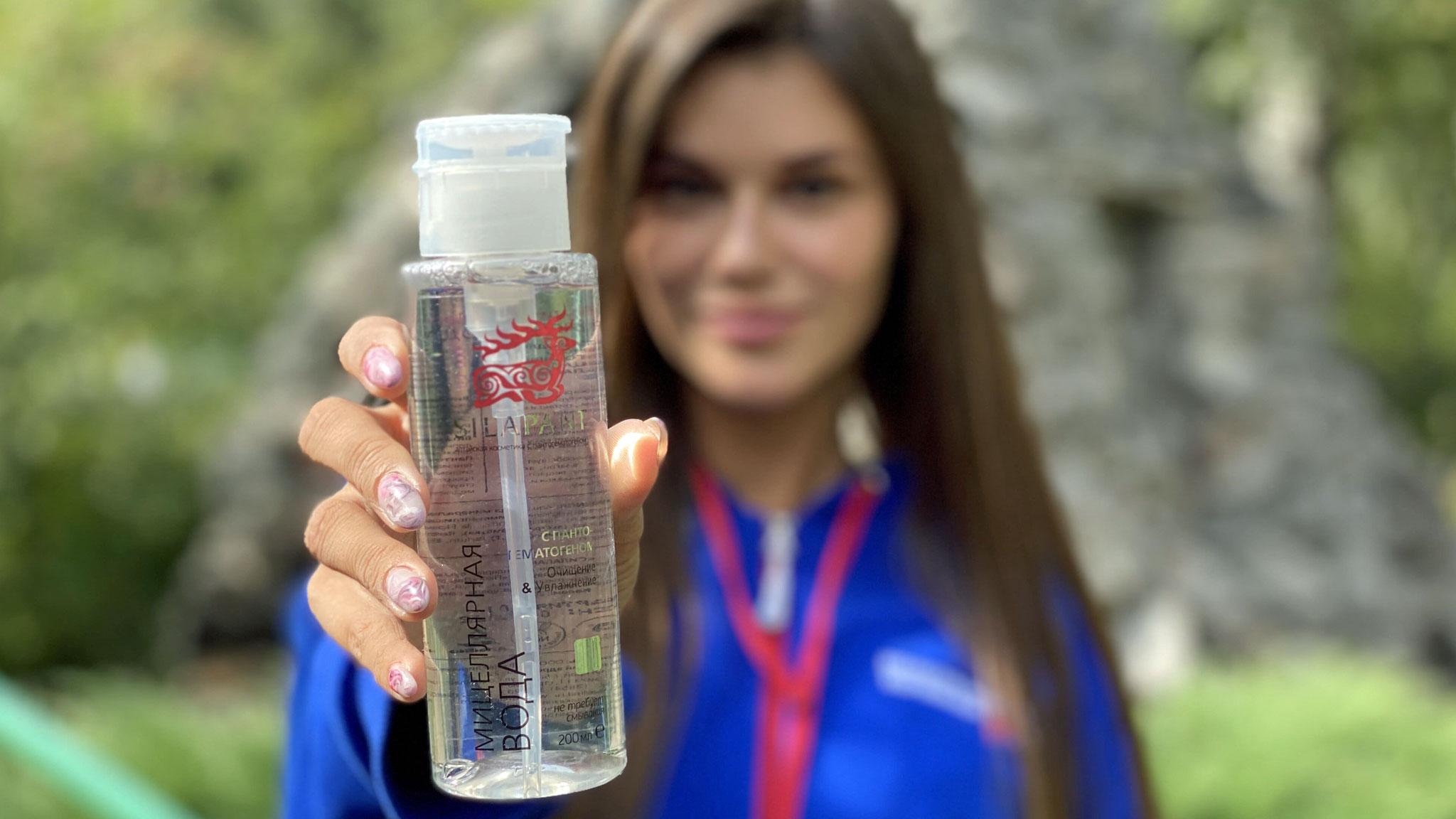 девушка держит бутылочку с лосьоном